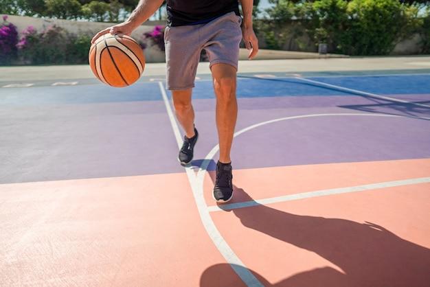 バスケットボール場でボールをドリブルするプロバスケットボール選手の脚