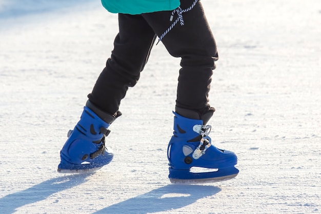 ストリートアイススケートリンクでのアイススケートのスケーターの足。冬のスポーツ。スポーツの趣味とアクティブなレクリエーション。