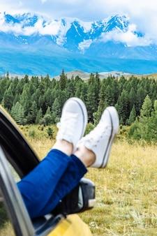 山への旅行で車に座っている旅行者の足