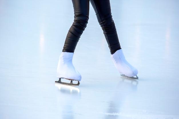 아이스 링크에서 스케이트를 타는 여자의 다리. 취미와 여가. 동계 스포츠
