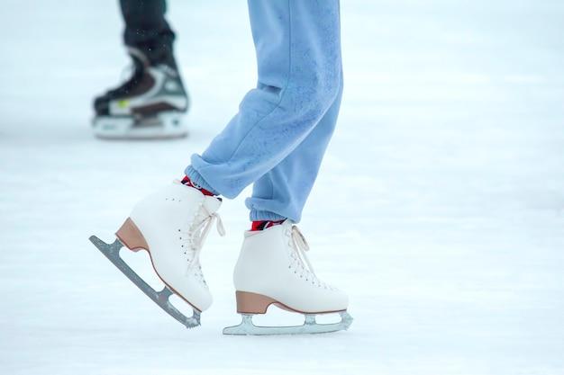 Ноги женщины на коньках на катке. хобби и досуг. зимние виды спорта
