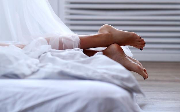 ベッドの中で女性の足