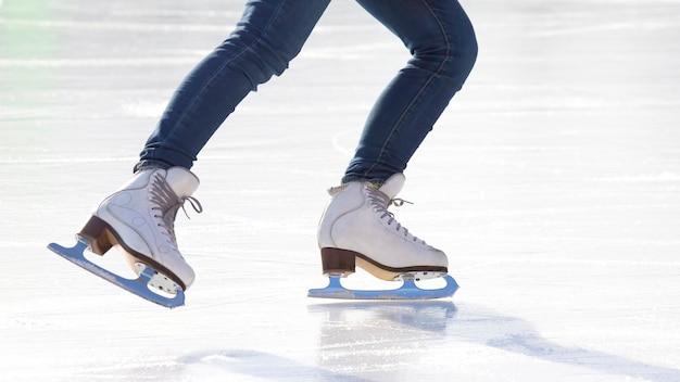 아이스 링크에서 청바지와 흰색 스케이트에 여자의 다리. 취미와 여가. 동계 스포츠
