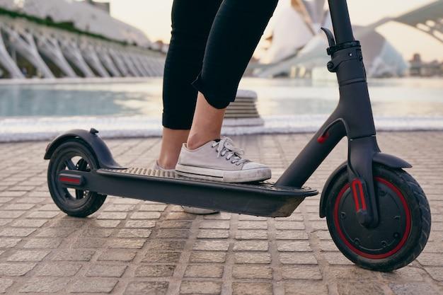 도시에서 전기 스쿠터를 타는 여자의 다리
