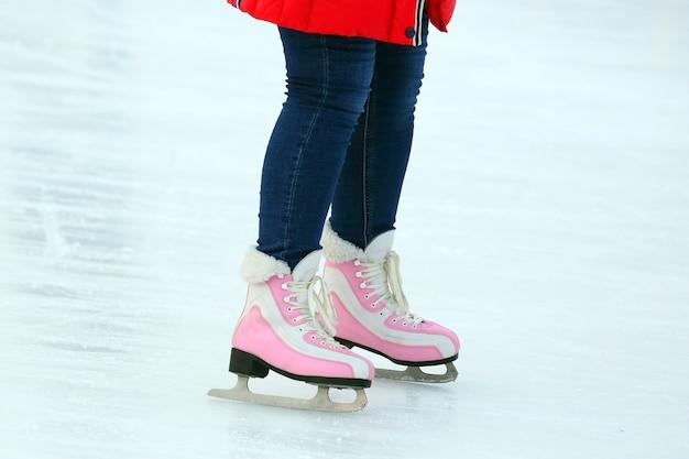 아이스 링크에서 스케이트를 타는 여자의 다리. 취미와 스포츠. 휴가 및 겨울 활동
