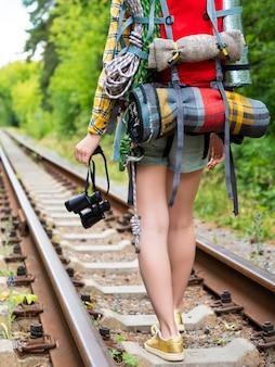 Ноги женщины с рюкзаком идут по железнодорожным путям с биноклем. вид сзади.