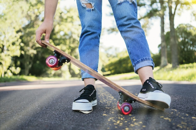 道路にスケートボードを持っている女性の足