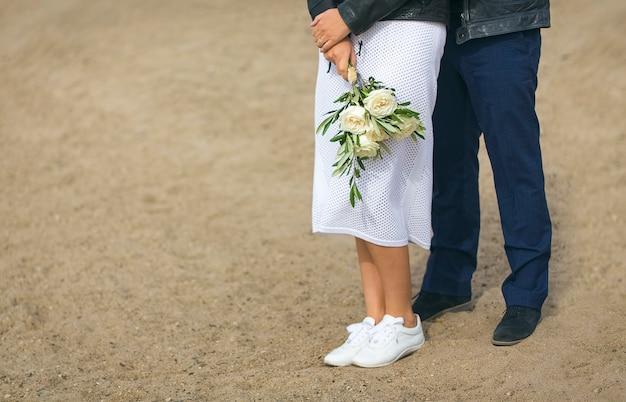 若いカップルの花嫁と花婿の足が砂の背景に立っています