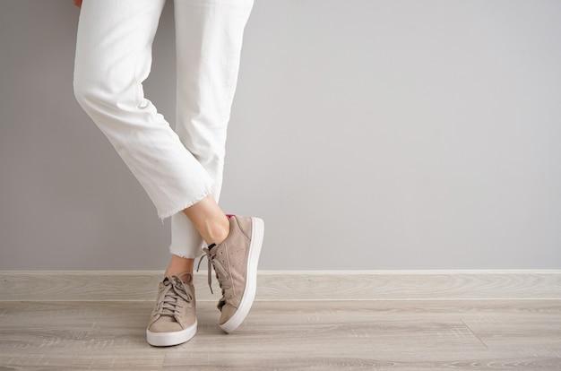 Ноги молодой девушки в джинсах и кроссовках на сером фоне, место для текста.