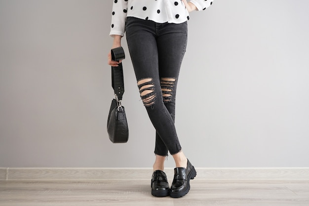 灰色の背景にバッグと靴とジーンズの少女の足。