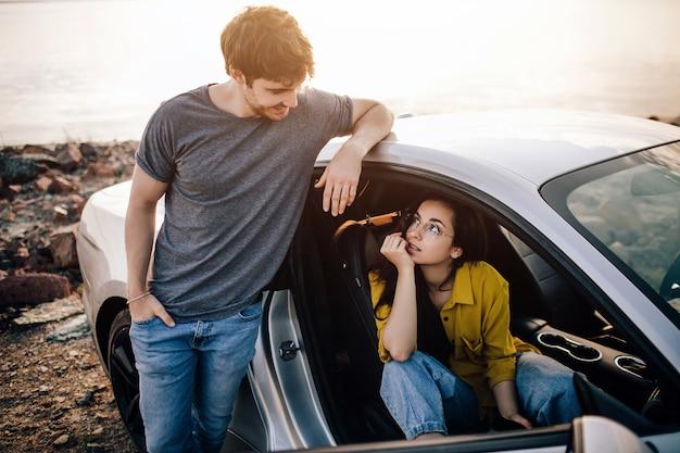 海の海岸の背景にある車の窓に白いブーツを履いた少女の足が平らに横たわっていた。楽しみ、観光でのリラクゼーション、旅行、自由な時間、休息、幸福の概念。