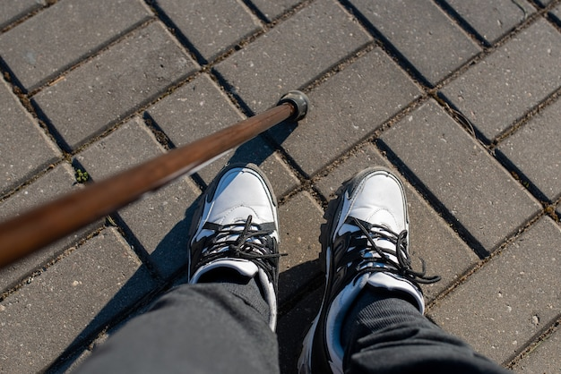 スニーカーを履いた若い男の足。杖を持って歩く。あらゆる目的のために。