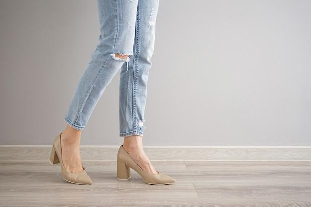 灰色の背景、テキストのためのスペースにジーンズと靴の若い女性の足。