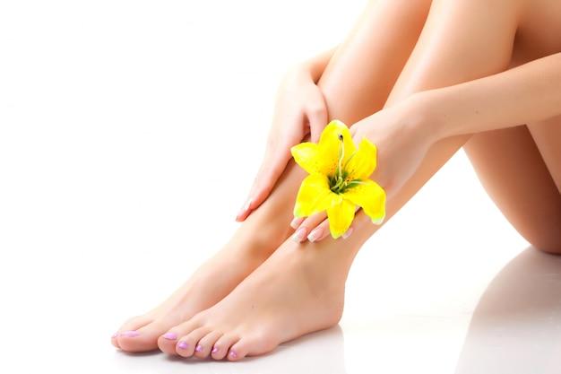 Ноги молодой женщины с цветком в руке