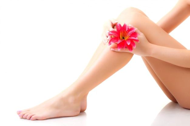 Ноги молодой женщины с красным цветком в руке