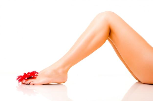 Ноги молодой женщины с красным цветком
