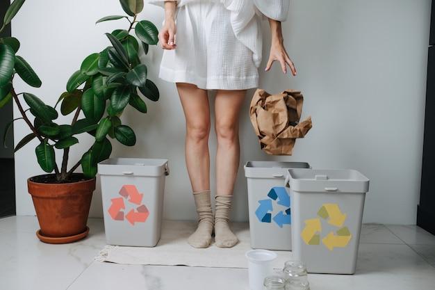 Ноги женщины сортируют мусор, бросают дома кусок скомканной упаковочной бумаги в маленькую корзину. их несколько, со стрелками разного цвета.