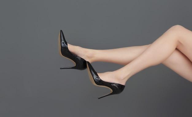 Ноги красивой молодой женщины в туфлях на высоких каблуках на сером