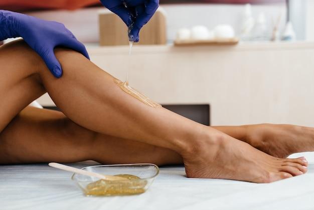 Ноги красивой молодой женщины с нанесенной сахарной пастой в салоне
