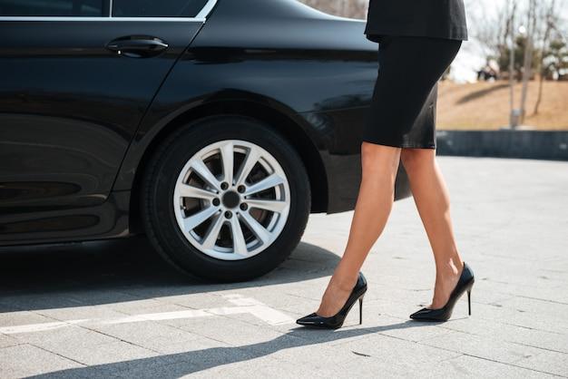 車の近くを歩くハイヒールの靴で実業家の足