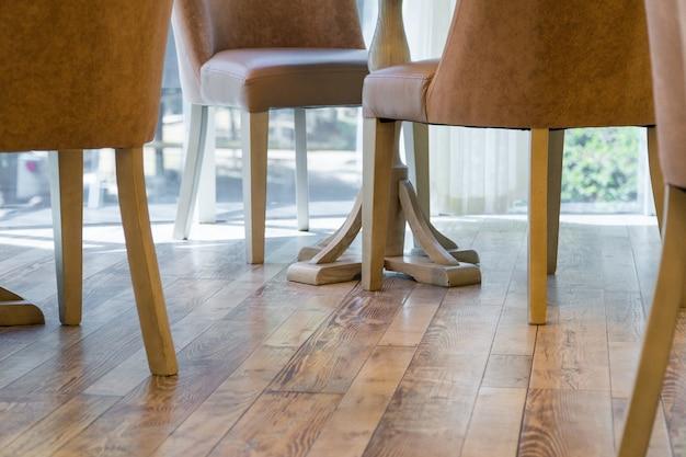 Ножки стульев на деревянном полу ресторана, крупный план