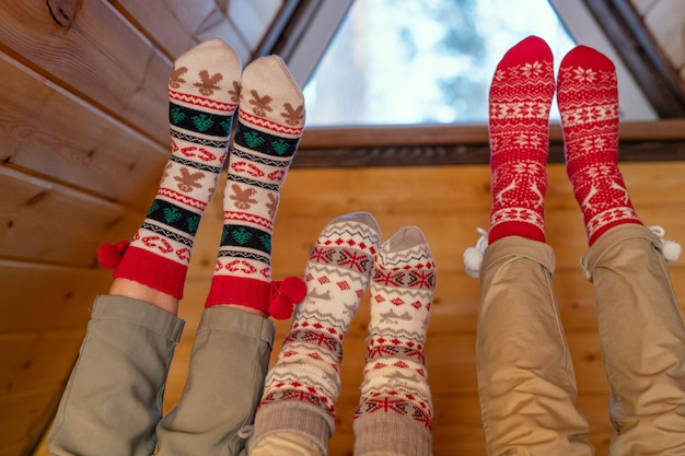 Ноги современной спокойной семьи отца, матери и маленькой дочери в бежевых джинсах и рождественских носках, расслабляющихся в своем загородном доме