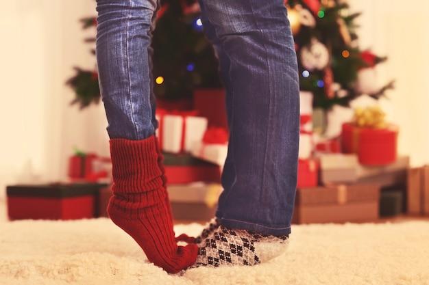 クリスマスツリーとプレゼントボックスのある部屋の毛皮のカーペットの上のカップルの足
