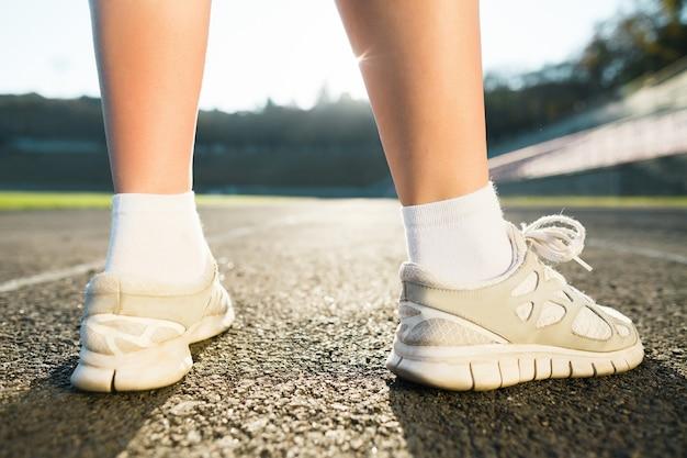 Ноги девушки в белых кроссовках и носках, стоя на земле, без лица, вид сзади. спортивная концепция, спортивная экипировка, стадион