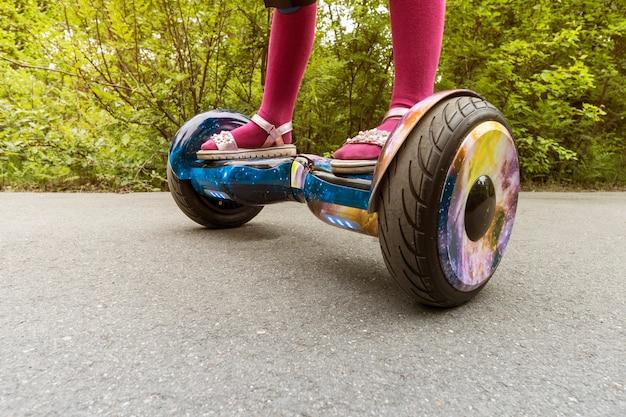 도시 공원에서 자가 균형 미니 호버보드를 타고 있는 소녀의 다리. 전자 스쿠터 야외 - 개인 휴대용 에코 운송, 자이로 스쿠터, hyroscooter, 스마트 밸런스 휠, 미니 세그웨이