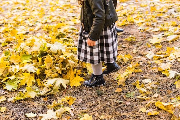 秋の背景の少女の足。