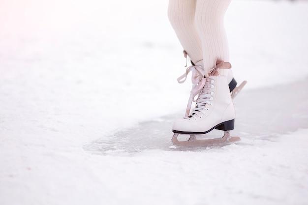 夜明けの朝の光の中で氷の上でスケートをする少女の足。ウィンタースポーツ