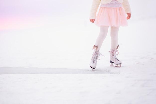 夜明けの朝の光の中で氷の上でスケートをする少女の足。