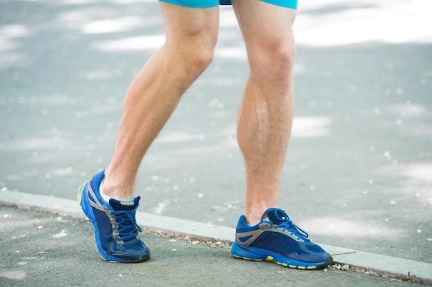 공원 보도를 조깅하는 남자 선수 주자의 다리. 액티브 라이프스타일 트레이닝 유산소 운동화. 혈관 질환 정맥류는 활동적인 삶에 문제가 있습니다. 정맥류 개념을 예방하십시오. 달리기로 인한 질병.