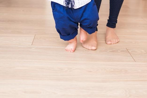 母親と赤ちゃんの足。最初のステップ。