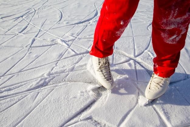 屋外の冬のアイススケートリンクのスケーターの足