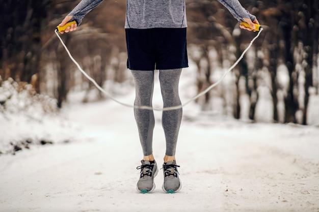 雪の降る冬の日に森の中で縄跳びをするスポーツマンの足。冬のフィットネス、雪の天気