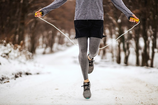 雪の降る冬の日に森の中で縄跳びをするスポーツマンの足。