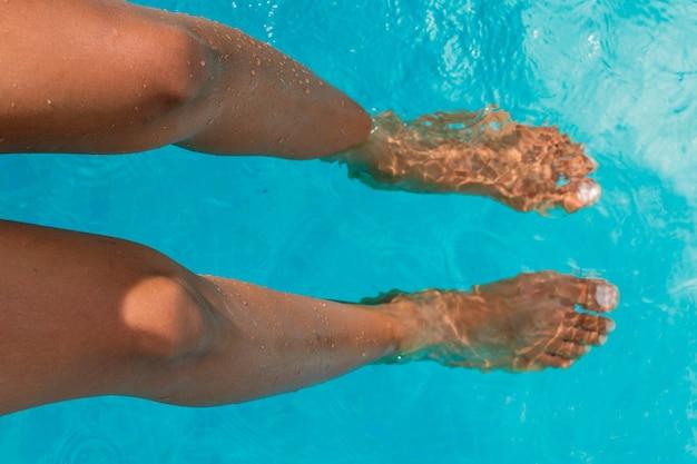 Ноги загорелой женщины в бассейне