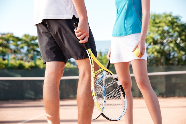 コートでテニスカップルの足。トリミングされた画像