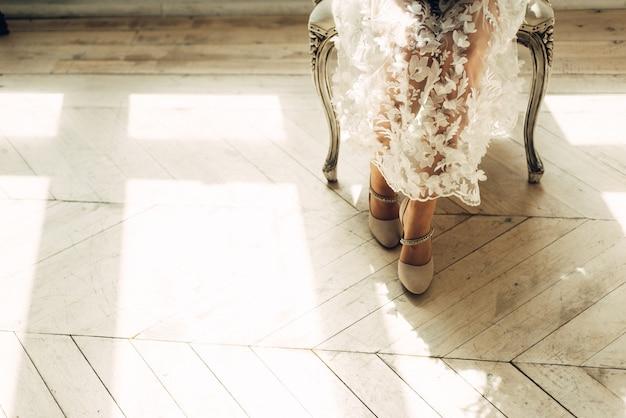 椅子に座っている花嫁の足、日光、空きスペースのある明るいスタジオ