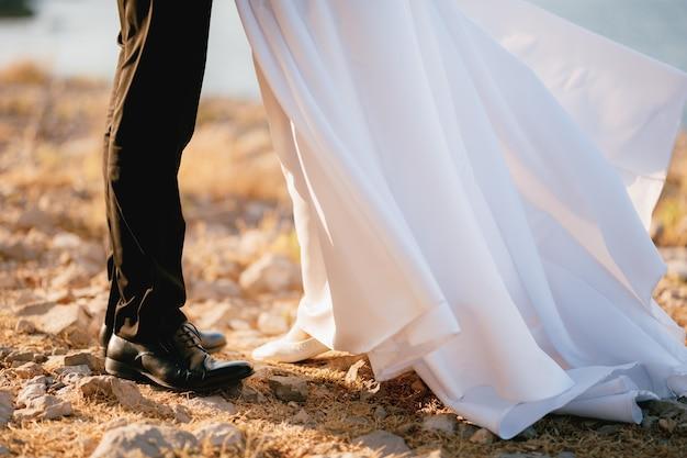 Ноги жениха и невесты в развевающемся платье, стоящие на каменистом пляже у моря.
