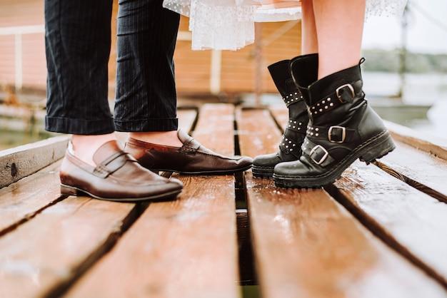 Ноги молодоженов на фоне пристани. жених и невеста стоят и позируют в сапогах на пристани.