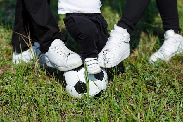 Ноги маленького сына, мамы и папы на мяче