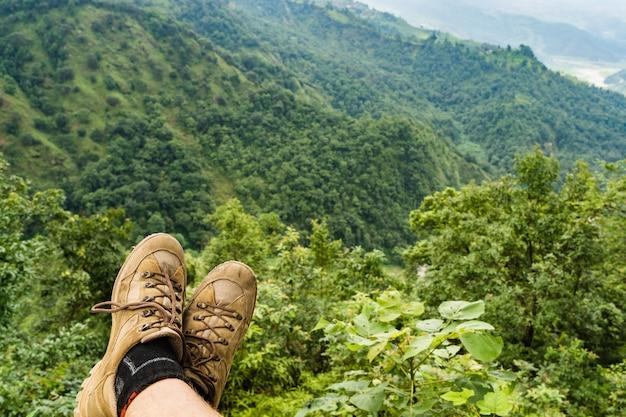 Ноги путешественника в походной обуви, сидя на высокой горной скале, наслаждаясь хорошим видом. концепция путешествий, свободы, треккинга и походов. запасное фото