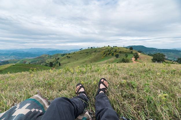 田舎の緑の丘でリラックスする旅行者の足