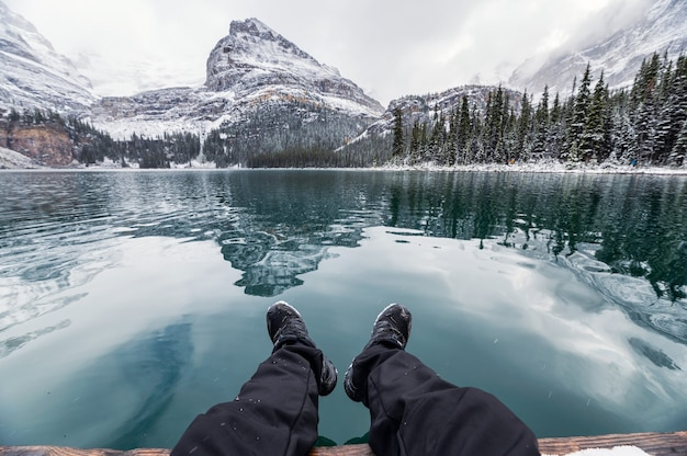 カナダ、ヨーホー国立公園の冬にオハラ湖に岩山が反射し、桟橋でくつろぐ旅行者の足