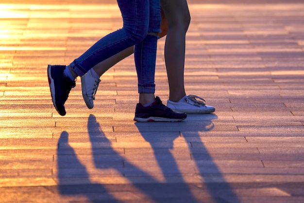 햇빛을 배경으로 걷는 두 사람의 다리. 우정과 관계의 동기화
