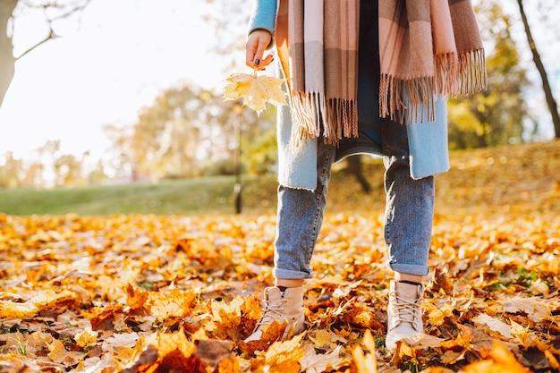 公園や森を歩いている秋の黄色の葉で茶色のブーツとジーンズを身に着けている認識できない女性の足