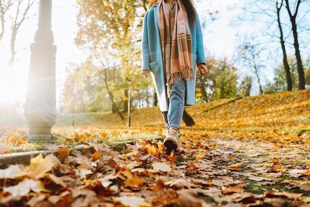 公園や森を歩いている秋の黄色の葉で茶色のブーツとジーンズを身に着けている認識できない女性の足。
