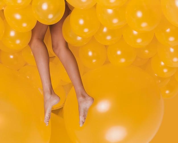 Ноги женщины между много желтых воздушных шаров
